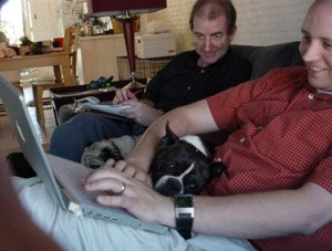 A field study facilitator watching a participant at home using a laptop to access a website, with a dog on the participant's lap.
